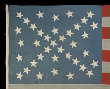 38 STARS IN A DYNAMIC STARBURST CROSS, ONE OF THE MOST SPECTACULAR STAR CONFIGURATIONS IN FLAG COLLECTING, ON AN ANTIQUE AMERICAN FLAG WITH POSSIBLE CONFEDERATE SYMPATHIES, COLORADO STATEHOOD, 1876-1889