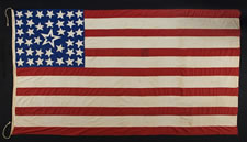 39 STARS IN A LINEAL PATTERN WITH A HUGE, HALOED CENTER STAR AND DYNAMIC VISUAL FEATURS, ITS CANTON RESTING ON THE WAR STRIPE, PROBABLY MADE FOR THE 1876 CENTENNIAL OF AMERICAN INDEPENDENCE, NEVER AN OFFICIAL STAR COUNT, REFLECTS THE ANTICIPATED ARRIVAL OF THE DAKOTA TERRITORY
