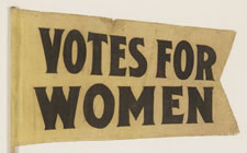 "SMALL, TAPERED, FORKED TAIL SUFFRAGETTE PENNANT ON ITS ORIGINAL WOODEN STAFF WITH TEXT THAT READS ""VOTES FOR WOMEN"", CA 1910-1920"