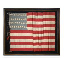 34 STARS ON AN EARLY CIVIL WAR FLAG (1861-1863) WITH ITS CANTON RESTING ON THE WAR STRIPE, AN UNUSUAL ELONGATED FORM; AN ATTRACTIVE SHADE OF BLUE, AND LARGE, MAKE-DO TASSELS