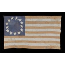 HOMEMADE FLAG WITH 13 STARS ARRANGED IN THE CIRCULAR WREATH PATTERN OFTEN ATTRIBUTED TO BETSY ROSS, WITH ENDEARING WEAR, AND WITH ITS CANTON RESTING ON THE WAR STRIPE, CA 1890-1920's