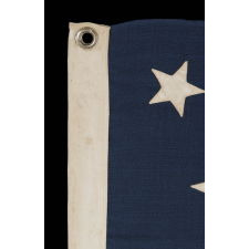 "13 STARS ARRANGED IN A MEDALLION PATTERN, WITH A SLIGHTLY LARGER CENTER STAR, ON A SMALL-SCALE ANTIQUE AMERICAN FLAG MARKED ""NAVY"" [A BRAND NAME], MADE DURING THE LAST DECADE OF THE 19TH CENTURY"
