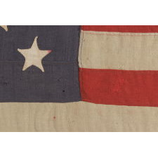 13 STARS ARRANGED IN A 3-2-3-2-3 PATTERN ON A BEAUTIFUL DUSTY BLUE CANTON, ON A SMALL-SCALE ANTIQUE AMERICAN FLAG MADE BETWEEN THE MID-1880'S AND 1890'S