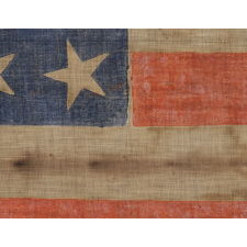 34 STARS WITH SCATTERED ORIENTATION ON A RARE, LARGE SCALE, CIVIL WAR PERIOD PARADE FLAG WITH ENDEARING WEAR FROM OBVIOUS EXTENDED USE, KANSAS STATEHOOD, 1861-63