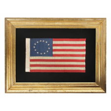 13 HAND-EMBROIDERED STARS AND EXPERTLY HAND-SEWN STRIPES, ON A FLAG MADE BY RACHEL ALBRIGHT, GRANDDAUGHTER OF BETSY ROSS, IN PHILADELPHIA IN 1903, A VERY LARGE EXAMPLE AMONG ITS COUNTERPARTS, WITH A STAR CONFIGURATION THAT IS MORE OVAL THAN CIRCULAR