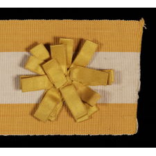 "SILK SUFFRAGETTE SASH RIBBON IN YELLOW & WHITE WITH ""VOTES FOR WOMEN"" TEXT AND A SATIN RIBBON ROSETTE, 1910-1915"