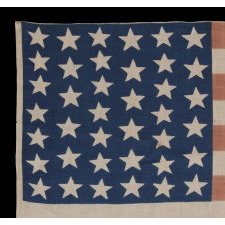 39 STARS IN TWO SIZES, ALTERNATING FROM ONE COLUMN TO THE NEXT, ON AN ANTIQUE AMERICAN PARADE FLAG DATING TO THE 1876 CENTENNIAL, NEVER AN OFFICIAL STAR COUNT, REFLECTS THE ANTICIPATED ARRIVAL OF THE DAKOTA TERRITORY