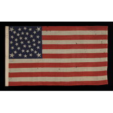 38 STARS ON AN EXTRAORDINARY ANTIQUE FLAG MADE FOR THE 1876 CENTENNIAL EXPOSITION, LIKELY BY THE HORSTMANN COMPANY IN PHILADELPHIA, WITH AN EXTREMELY RARE FORM OF THE MEDALLION CONFIGURATION THAT BEARS AN ELLIPSE OF 6 STARS IN THE CENTER AND A LARGE STAR IN EACH CORNER; REFLECTS COLORADO STATEHOOD