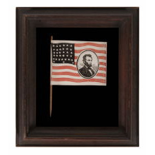 "EXTREMELY RARE ABRAHAM LINCOLN MOURNING FLAG, WITH HIS PORTRAIT IN THE STRIPED FIELD, ON ITS ORIGINAL STAFF; PRINTED ON PAPER, SIGNED ""LYBRAND,"" 1865"