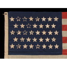 38 STARS WITH ENDEARING WEAR ON AN UNUSUALLY SMALL PIECED-AND SEWN ANTIQUE AMERICAN FLAG OF THE 1876-1889 PERIOD, REFLECTS COLORADO'S ADDITION TO THE UNION