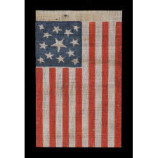 13 STAR AMERICAN PARADE FLAG MADE BETWEEN THE CIVIL WAR (1861-65) AND THE 1876 CENTENNIAL OF AMERICAN INDEPENDENCE, FEATURING THREE SIZES OF WHIMSICALLY SHAPED STARS IN A MEDALLION CONFIGURATION