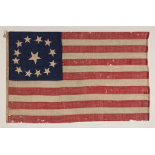 13 LARGE STARS WITH AN EVEN LARGER CENTER STAR, IN A CIRCULAR VERSION OF WHAT IS KNOWN AS THE 3RD MARYLAND PATTERN, ENTIRELY HAND-SEWN, MADE SOMETIME BETWEEN 1850 AND THE CIVIL WAR (1861-65), AN EXCEPTIONAL EXAMPLE WITH WONDERFUL FOLK QUALITIES