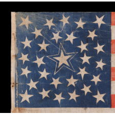 31 STARS ON AN ANTIQUE AMERICAN FLAG WITH ITS STARS CONFIGURED IN A MEDALLION PATTERN THAT FEATURES A LARGE, HALOED CENTER STAR; REFLECTS THE PERIOD WHEN CALIFORNIA HAD RECENTLY BECOME THE 31ST STATE TO ENTER THE UNION, 1850-1858